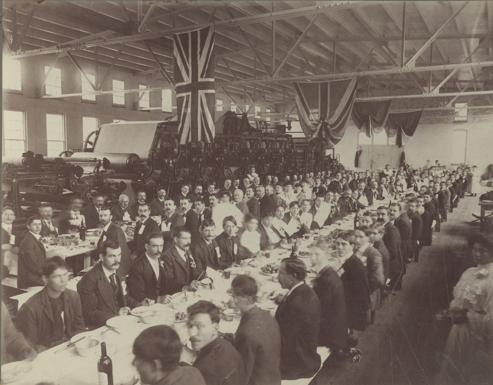 Black & white photograph showing several people seated at long tables in a factory setting. A paper-making machine stands in the background.