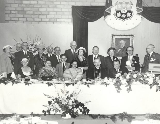 Black & white photograph of a head table group at a celebration.