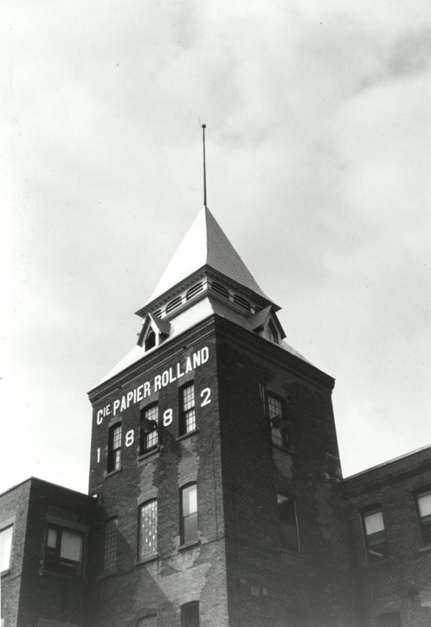 Black & white photograph showing a tower above a building.
