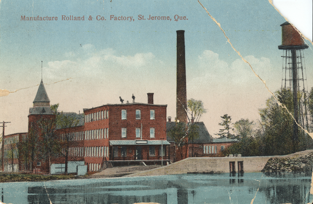 Colour image of buildings close to a large chimney stack and a river.