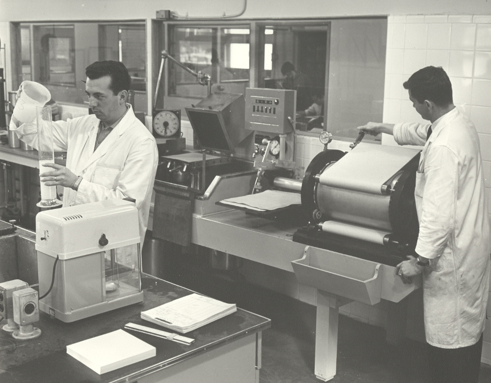 Black & white photograph showing two men in white coats in a laboratory.