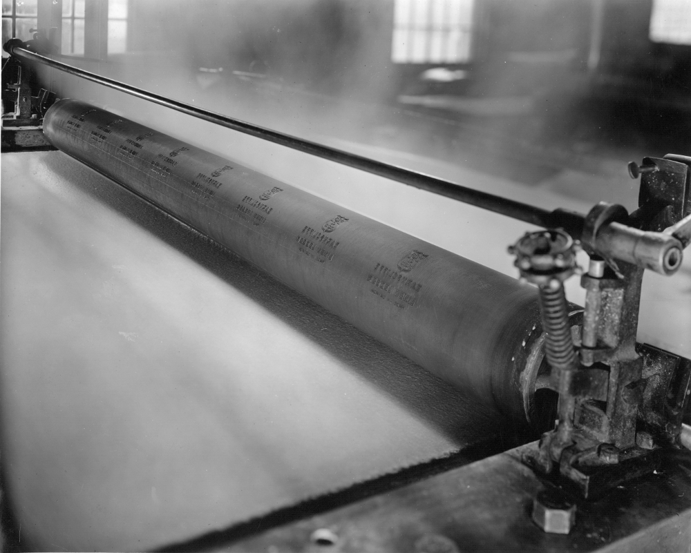 Black & white photograph of a long roll with a sheet of paper passing below it.