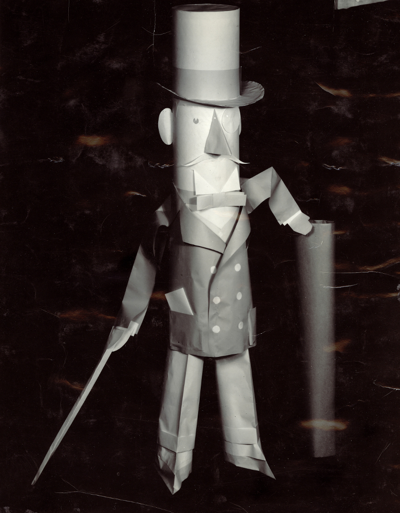Black & white photograph of a character in a suit with a top hat made of paper.