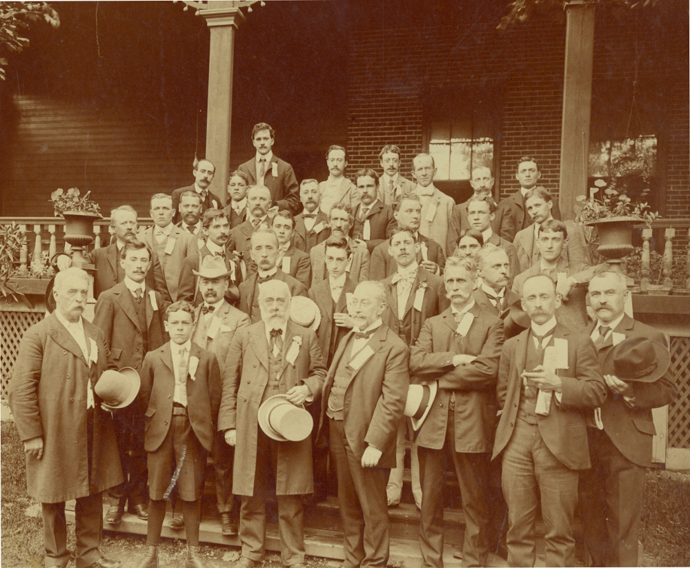 Sepia-tone photograph showing a group of men clad in suits, on stairs in front of a house.