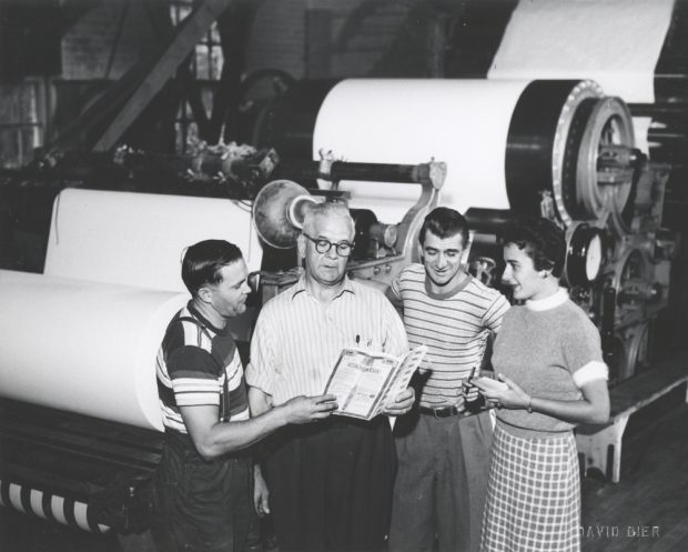 Black & white photograph showing four people in front of a paper-making machine.