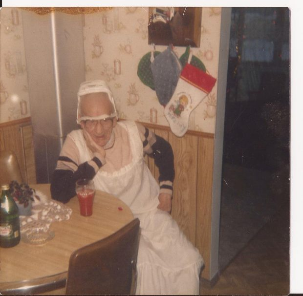 A male mummer in a nightgown and wearing a lampshade on his head sits at a table having a drink