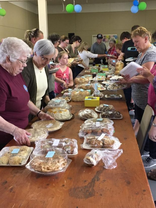 Baked goods are displayed on a table surrounded by customers waiting for the start of a bake sale