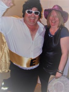 A man dressed as Elvis and a woman prepare for a concert