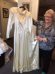 An elderly woman proudly shows her white satin wedding dress