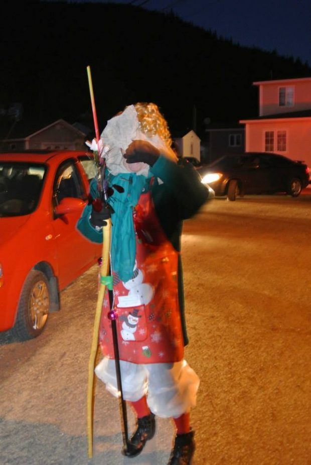 One mummer walks outside with a stick in a night time mummers parade