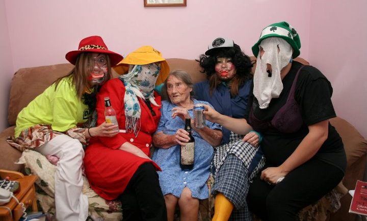 Four Mummers having a nip of rum sit with an elderly woman on a crowded couch
