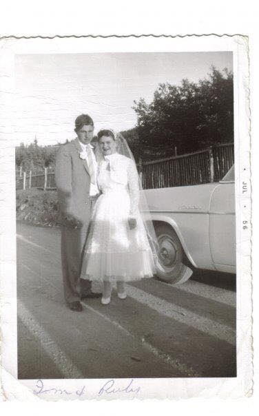 Bride and groom stand next to a white truck