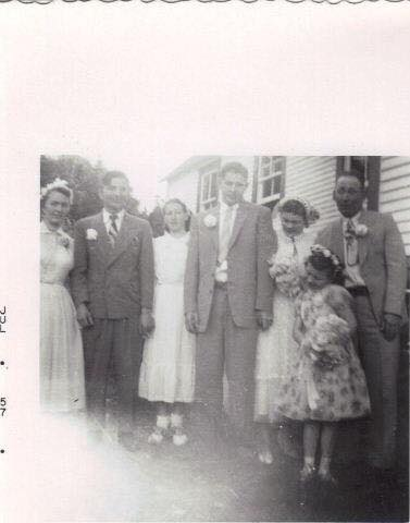 A bridal party stands outside a community hall