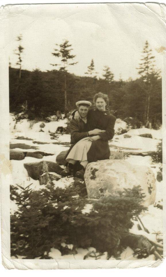 A man and a woman sit together on a rock in a brook