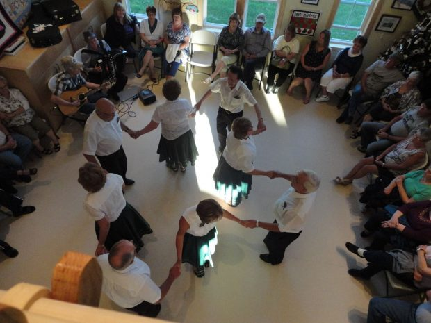 A group of men and women of the Little Bay heritage dancers performing a square dance