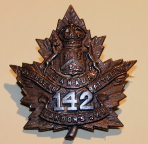 A badge in the shape of a maple leaf with a shield surmounted by a crown supported by two deer, scrolls and number 142.
