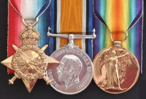 Three medals, mounted to bright coloured ribbons as follows (from left to right): first medal is golden shade, in the shape of a 4-pointed star, surmounted by a crown suspended to the ribbon by a ring, and with 2 swords intersected across; a laurel wreath is superimposed; second medal is silver shade, round shaped suspended to the ribbon on a bar; in the centre of the medal, a male profile looking to the left; the third medal is golden shade, round shaped, suspended to the ribbon by a ring; in the centre the image of a winged female, symbol of Victory.