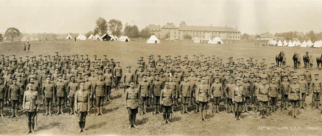 Photograph of a large group of military, all male, in the foreground. Tents, horses and a building in the background.