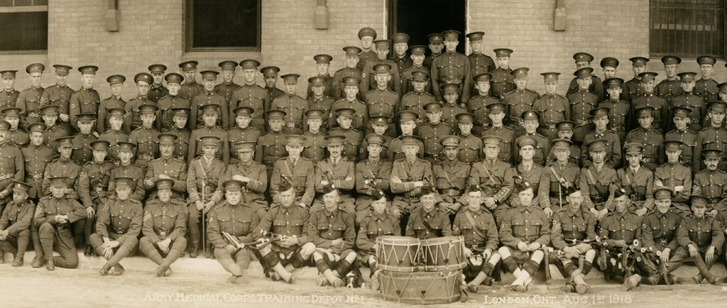 Photograph of a large group of military, all male, sitting and standing.Three drums in front and architecture details in the background.