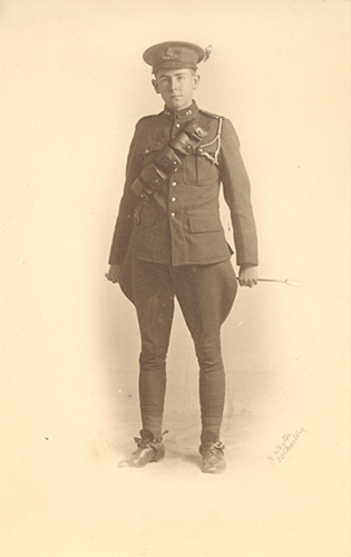 Photograph of a soldier standing and holding a whip behind with both his hands.