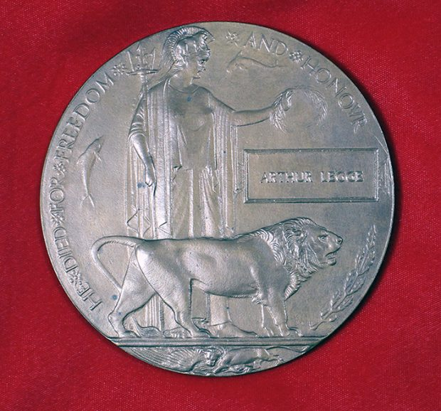 A circular brass plaque with the image of a women holding laurel leaves and a lion in front of her.