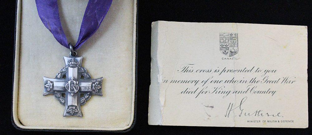 Une boîte contenant une croix en argent accrochée à un ruban pourpre et une carte signée par le ministre de la Milice et de la Défense.