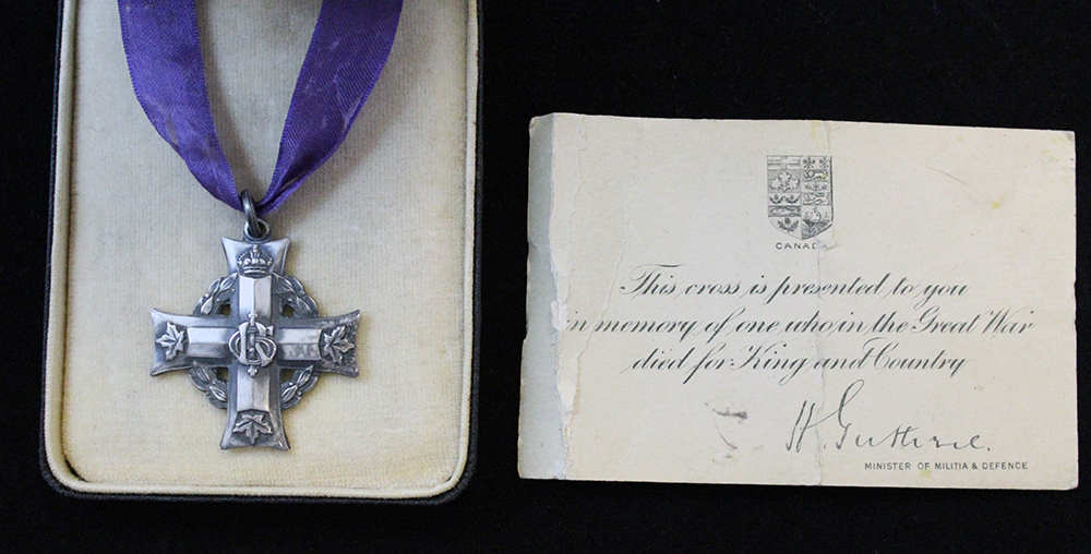 A box with a silver cross suspended to a purple ribbon and a card signed by the Minister of Militia and Defence.