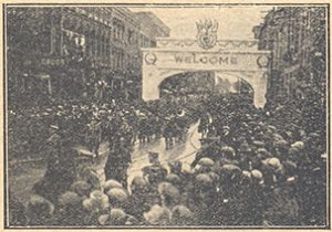 Crowds cheer soldiers passing under an arch.