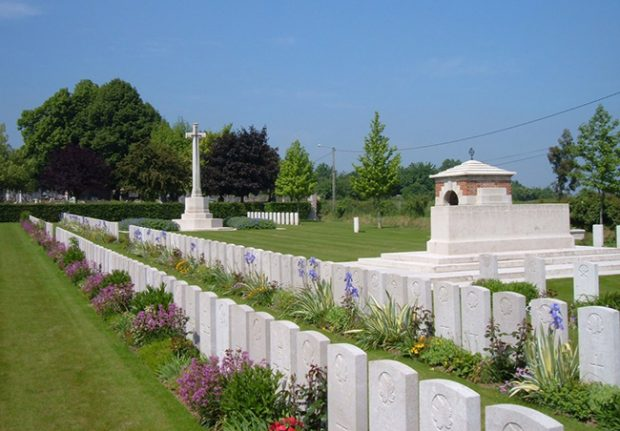 Photograph of a military cemetery with headstones in 2 rows surrounded by flowers. A large cross and the back of a munument are shown in the background.