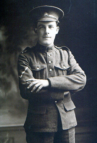 A soldier wearing a peak hat, with his arms in front oh his chest.