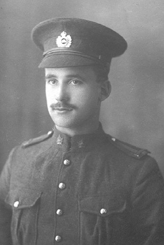 Portrait of a soldier wearing a peak hat. He has a moustache. Chest pockets, buttons and collar dogs can be seen.