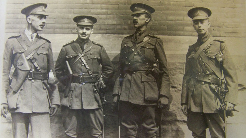 Four males, military officers standing and talking in front of a building. Second from right holds his hands behind his back. They all have pistol holsters and swords.