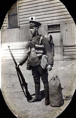 The image of a soldier standing in an oval mat. He is holding his rifle with his right hand. A duffel bag is beside his left foot. A building is seen behind.