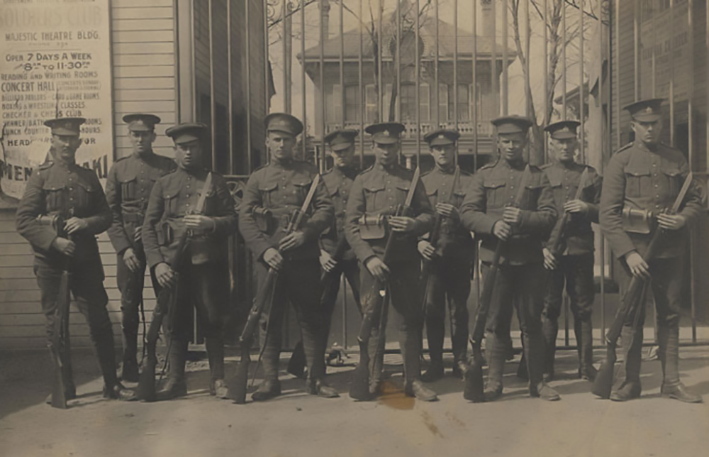 Ten soldiers, all wearing a peak hat and holding rifles. They stand in front of a grill gate, a fragment of a sign for a theatre can be seen on the right.