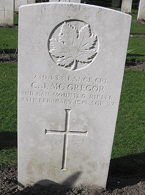 A grave stone with a cross and maple leaf.
