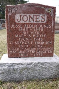 A rectangular grave stone with little ornament and the word JONES carved in.