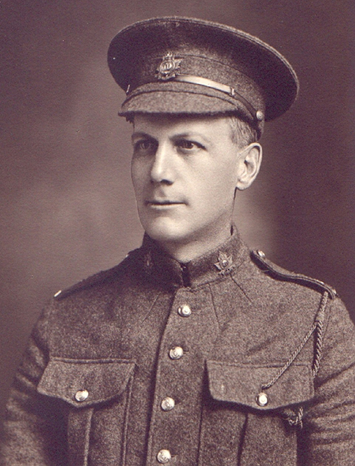 Portrait of a soldier wearing a peak hat. Chest pockets, buttons and collar dogs can be seen.