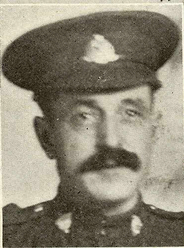 Portrait of a soldier wearing peak hat. He has a moustache.