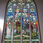 Un vitrail monumental dans une église, formé de 4 panneaux centrales surmontés des motifs décoratifs gothiques qui se termine en ogive.