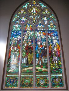 A monumental stained glass in a church, formed of 4 main panels, surmounted with Gothic ornaments closed in a pointed arch (ogive).