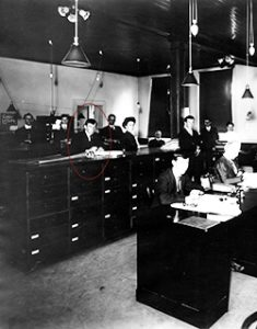 Photograph of an office with tall desks, 9 males and 1 female workers.