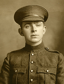 Portrait of a soldier wearing a peak hat. Chest pockets and buttons can be seen.