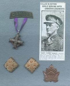 A silver Greek cross suspend to a metal plaque by a purple ribbon. Two small, diamond shaped embroidery (pips) and a brass maple leaf with a crown and the word CANADA. The photograph of a soldier wearing a peak hat is at the top right.