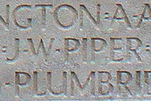 Fragment of a stone grave with upper case letters engraved. The word PIPER is visible.