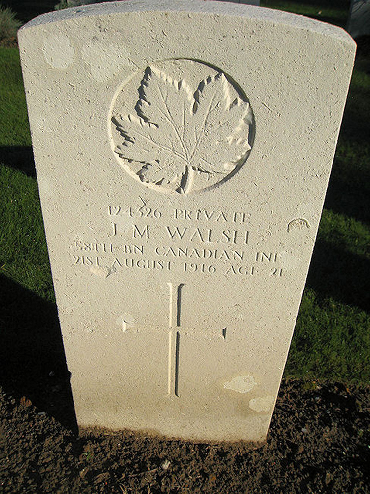 A grave stone with a cross and a maple leaf.
