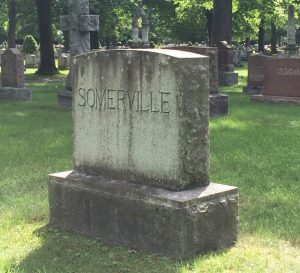 """Photograph of a headstone in a cemetery. The name """"SOMERVILLE is carved on it."""