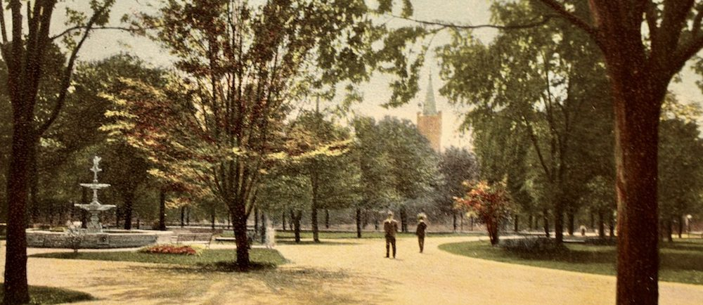 Post card of a park. A fountain can be seen at the left and the tower of a church in the background. The inscription View of Victoria park, London, Ont. on the lower right.