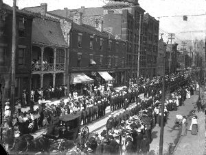 A military parade on the street of a city. The parade is lead by a carriage with 2 horses, the soldiers are marching in 2 rows. Crowds watch on the sidewalk.