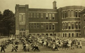 Photograph of a building and children exercising.