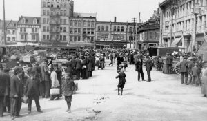 Photograph of people at the market, children playing and buildings.